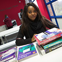 Student sitting at desk with books