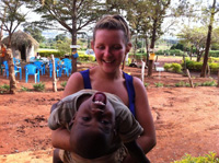 Student Volunteer with child in Uganda