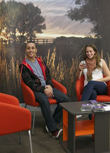 Male and female student using social space in Brackenhurst Library