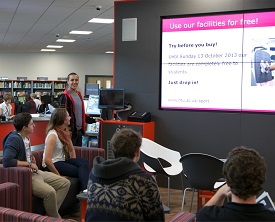 Male student using video wall with group in Brackenhurst Library