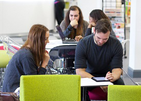 Male and female students studying in social seating area in Clifton Library