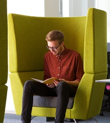 Male student reading in comfy chair on Level 1 of Clifton Library