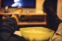 Popcorn in a bowl and peoples feet resting on table - Credit: Movie Night by Ginny, 2010, licensed under CC BY-SA 2.0