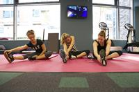 3 girls stretching on gym mats in new city sports gym