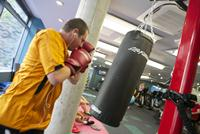 student using punch bag in city gym