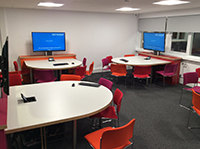 Classroom with large semicircular tables each with a pc with a large monitor