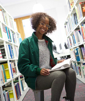 Female student sitting amongst library shelves in Boots Library Level 2