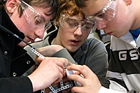 3 students working on a technology model