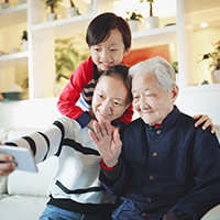 Young boy taking photo with his mother and grandfather