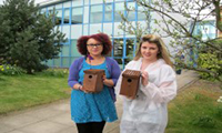 2 people holding bird boxes